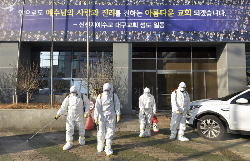 In this Wednesday, Feb. 19, 2020, photo, workers wearing protective gears spray disinfectant against the coronavirus in front of a church in Daegu, South Korea. The mayor of the South Korean city of Daegu urged its 2.5 million people on Thursday, Feb. 20, to refrain from going outside as cases of a new virus spike. (Lee Moo-ryul/Newsis via AP)