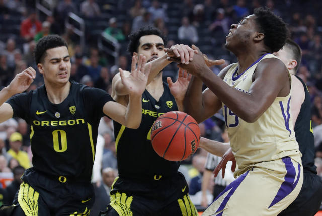 Oregon's Will Richardson, left, and Ehab Amin guard Washington's Noah Dickerson during the first half of an NCAA college basketball game in the final of the Pac-12 men's tournament Saturday, March 16, 2019, in Las Vegas. (AP Photo/John Locher)