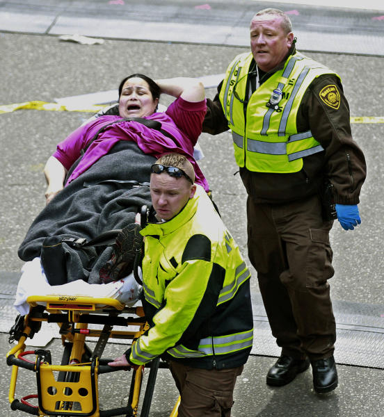 FILE - In this Monday, April 15, 2013 file photo, medical workers aid an injured woman at the finish line of the 2013 Boston Marathon following two explosions there. One week after the bombings, all of the more than 180 people injured in the blasts who made it to a hospital alive now seem likely to survive. The remarkable, universal survival of those injured is a testimonial to fast care at the scene, on the way to hospitals, then in emergency and operating rooms. (AP Photo/Charles Krupa, File)