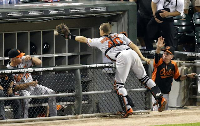 Baltimore Orioles catcher Nick Hundley is unable to catch a foul ball hit by Chicago White Sox's Alexei Ramirez, during the sixth inning of a baseball game Wednesday, Aug. 20, 2014, in Chicago. (AP Photo/Charles Rex Arbogast)