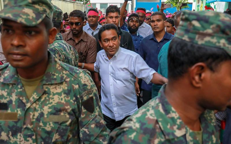 President Yameen Abdul Gayoom, center, surrounded by his body guards arrives to address his supporters in Male, Maldives - AP