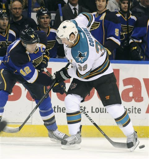 St. Louis Blues' David Backes (42) battles with San Jose Sharks' Logan Couture (39) in the first period of an NHL hockey game Tuesday, March 12, 2013, in St. Louis. (AP Photo/Bill Boyce)