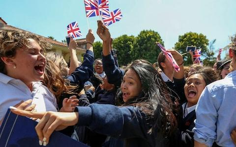 Students at Immaculate Heart High School and Middle school celebrate with British flags - Credit: DAVID MCNEW /AFP/Getty