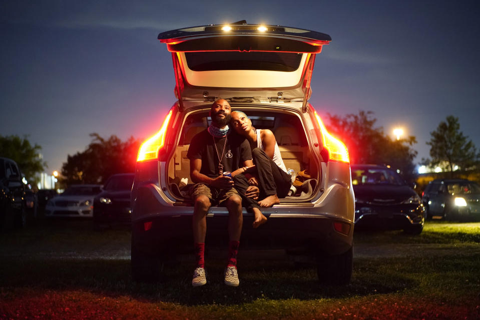 """Kene Daniels, right, and Amman Raheem watch a documentary called """"Rebuilding Black Wall Street,"""" during a drive-in screening of documentaries during centennial commemorations of the Tulsa Race Massacre, Wednesday, May 26, 2021, in Tulsa, Okla. (AP Photo/John Locher)"""