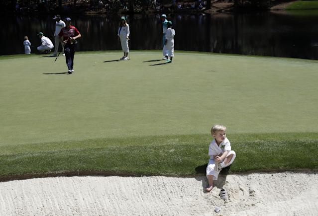 Webb Simpson's son James removes his shoes in a bunker while his father plays the par three competition at the Masters golf tournament Wednesday, April 9, 2014, in Augusta, Ga. (AP Photo/Chris Carlson)