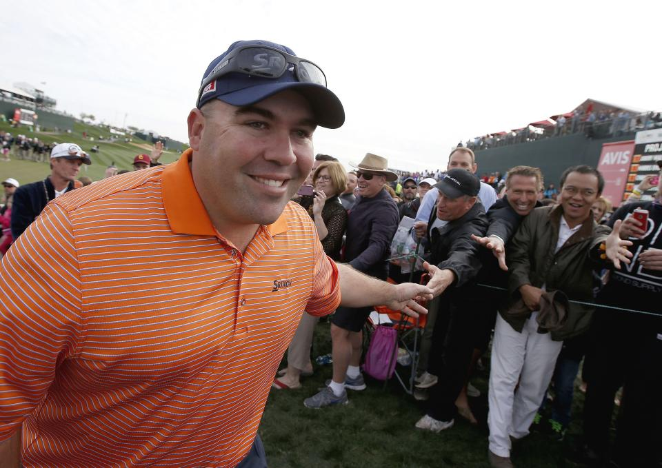 Kevin Stadler smiles as he gets handshakes from members of the gallery as he walks off the 18th green after winning the Phoenix Open golf tournament on Sunday, Feb. 2, 2014, in Scottsdale, Ariz. (AP Photo/Ross D. Franklin)