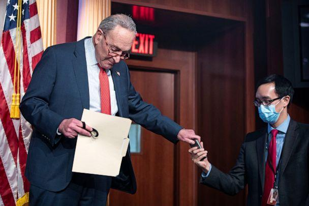 PHOTO: Senate Minority Leader Chuck Schumer hands his cell phone to an aide during a weekly news conference in Washington,Dec. 15, 2020. (Alexander Drago/Reuters)