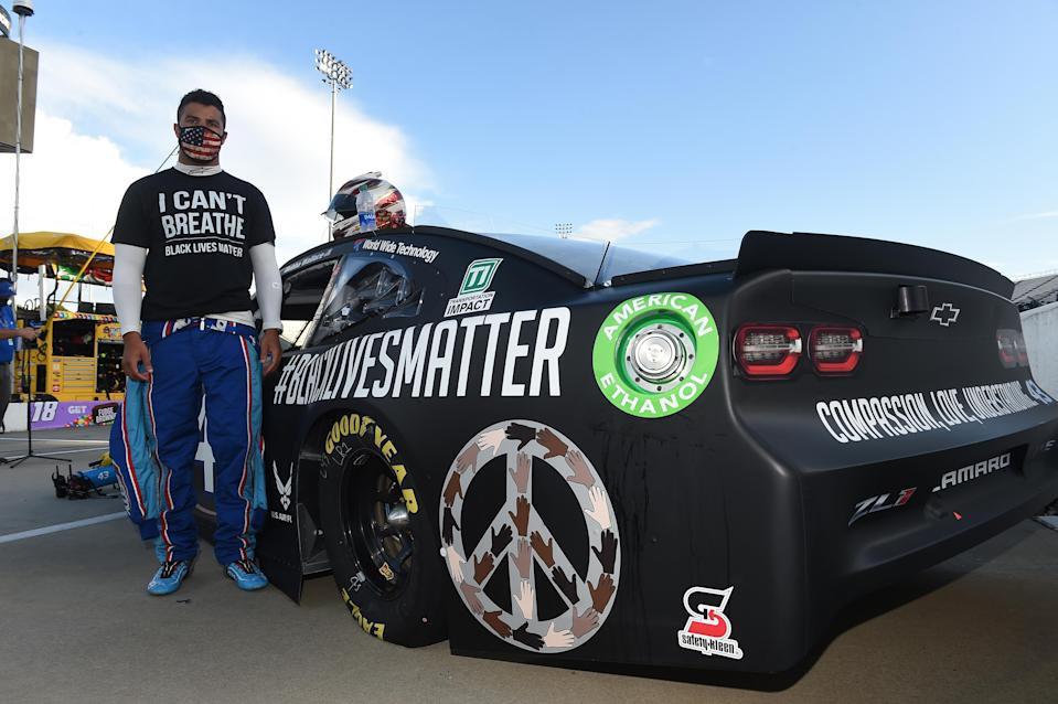 """Bubba Wallace, driver of the #43 Richard Petty Motorsports Chevrolet, wears a """"I Can't Breathe - Black Lives Matter"""" t-shirt under his fire suit in solidarity with protesters around the world taking to the streets after the death of George Floyd on May 25 , stands next to his car painted with """"#Black Lives Matter"""" prior to the NASCAR Cup Series Blue-Emu Maximum Pain Relief 500 at Martinsville Speedway on June 10, 2020 in Martinsville, Virginia. (Photo by Jared C. Tilton/Getty Images)"""