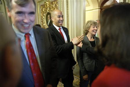 U.S. Senator Jeff Merkley (D-OR) (L-R), Senator Cory Booker (D-NJ) and Senator Tammy Baldwin (D-WI) celebrate with supporters after a vote to pass the Employment Non-Discrimination Act (ENDA), legislation to ban workplace discrimination against gays, at the U.S. Capitol in Washington November 7, 2013. REUTERS/Jonathan Ernst