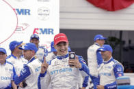 Alex Palou celebrates with his phone in the Winner's Circle after an IndyCar race at Road America in Elkhart Lake, Wisc., Sunday, June 20, 2021. (AP Photo/Jeffrey Phelps)