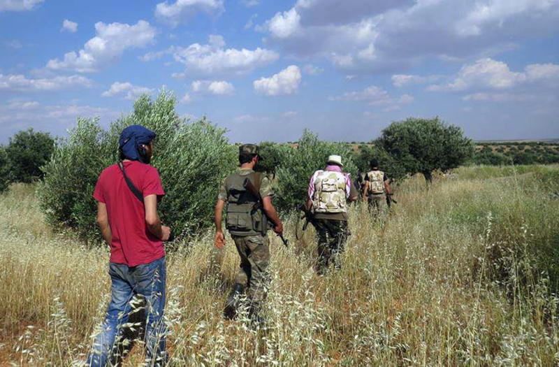 FILE - In this Tuesday, May 21, 2013 file photo citizen journalism image provided by Edlib News Network, ENN, which has been authenticated based on its contents and other AP reporting, shows Syrian rebels walking through a field in Idlib province, northern Syria. Syria's rebels have received shipments of more powerful weapons from Gulf allies, particularly anti-tank and anti-aircraft missiles, that have already helped stall advances by regime forces. The shipments have also sparked feuding and sniping between rebel factions, illustrating the tangles the United States faces as it prepares to start directly arming a rebellion riven by rivalries and competitions and dominated by Islamist radicals. (AP Photo/Edlib News Network ENN, File)