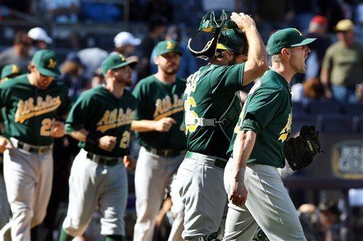 Oakland Athletics relief pitcher Grant Balfour, right, shouts to teammates after their 5-4 win over the New York Yankees in a baseball game in New York, Sunday, May 5, 2013. (AP Photo/Peter Morgan)