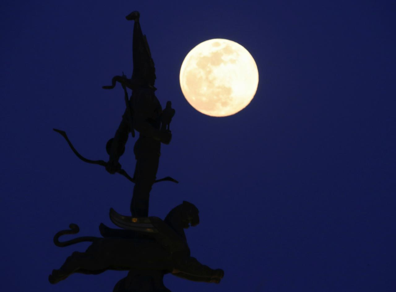 <p>The moon rises behind the Independence Monument in Almaty, Kazakhstan March 20, 2019. REUTERS/Pavel Mikheyev </p>