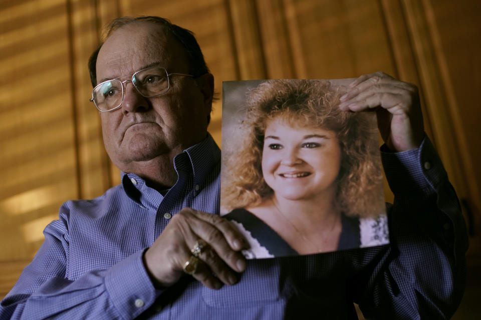 Mortuary owner Brian Simmons holds a photo of his daughter Rhonda Ketchum who died before Christmas of COVID-19, Thursday, Jan. 28, 2021, in Springfield, Mo. Simmons has been making more trips to homes to pick up bodies to be cremated and embalmed since the pandemic hit. For many families, home is a better setting than the terrifying scenario of saying farewell to loved ones behind glass or during video calls amid the coronavirus pandemic. (AP Photo/Charlie Riedel)