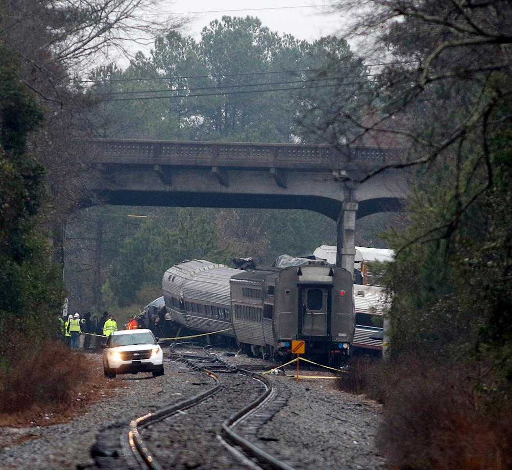 <p>Investigators make their way around the train wreckage under the Charleston Highway overpass in Cayce, SC where two trains collided early Sunday morning on Feb. 4, 2018. (Photo: Bob Leverone/Getty Images) </p>