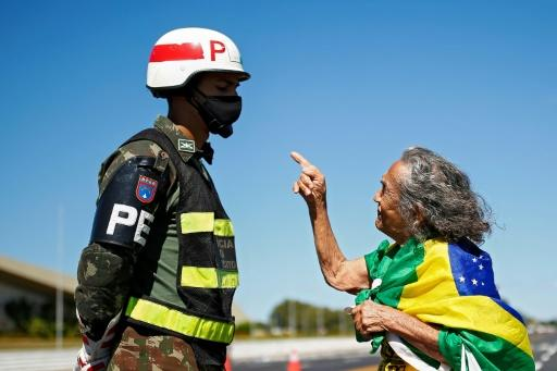 A supporter of the Brazilian president speaks to a soldier at a protest against a decision by Brasilia's governor to prevent crowds from attending Jair Bolsonaro's rallies