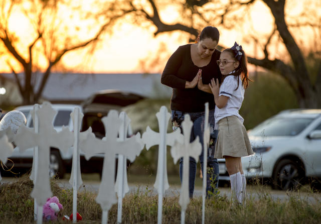 <p>Meredith Cooper, of San Antonio, Texas, and her 8-year-old daughter, Heather, visit a memorial of 26 metal crosses near First Baptist Church in Sutherland Springs, Texas, Monday Nov. 6, 2017. (Photo: Jay Janner/Austin American-Statesman via AP) </p>