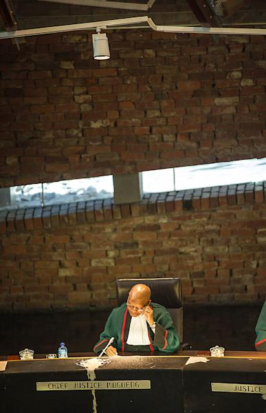 """South African chief Justice Mogoeng Mogoeng delivers the Constitutional Court verdict on President Jacob Zuma's conduct regarding his private residence on March 31, 2016 in Johannesburg, South Africa. President Jacob Zuma flouted the constitution in using public funds to upgrade his private residence and must repay the money, South Africa's top court ruled, sparking calls for his impeachment. The Constitutional Court delivered a damning verdict on Zuma's conduct after a swimming pool, chicken run, cattle enclosure and amphitheatre were built at his rural homestead as so-called """"security"""" measures. (AFP Photo/MUJAHID SAFODIEN)"""