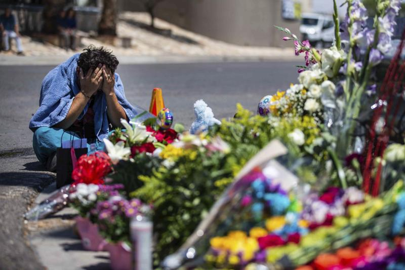 Felipe Avila puts his head in his hands as he cries Sunday, Aug. 4, 2019, in El Paso, Texas,at the place where locals came to honor the memory of the victims of the mass shooting occurred in Walmart on Saturday, Aug. 3, 2019. (Lola Gomez/Austin American-Statesman via AP)