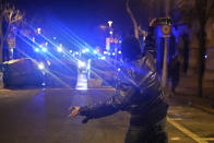 A demonstrator throws a bottle towards police vans during a protest condemning the arrest of rap singer Pablo Hasél in Barcelona, Spain, Saturday, Feb. 20, 2021. A fifth night of peaceful protests to denounce the imprisonment of a Spanish rap artist once more devolved into clashes between police and fringe group members who set up street barricades and smashed storefront windows in Barcelona. (AP photo/Joan Mateu, Pool)