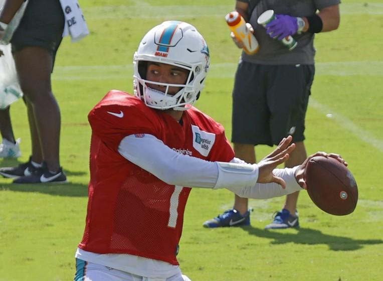 FILE - In this Aug. 18, 2020, file photo, Miami Dolphins quarterback Tua Tagovailoa (1) throws the ball during an NFL football training camp practice in Davie, Fla. If Brian Flores is to become the Miami Dolphins' first Super Bowl coach since Don Shula, he needs for Tua Tagovailoa to become their best quarterback since Dan Marino.(AP Photo/Joel Auerbach, File)