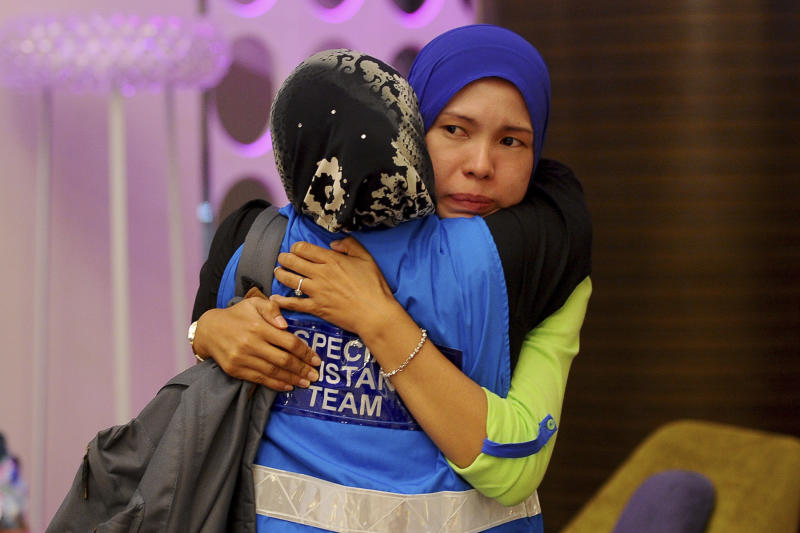 A family member, right, of passengers aboard a missing Malaysia Airlines plane is embraced by a member of Special Assistance Team at a hotel in Putrajaya, Malaysia, Tuesday, March 25, 2014. Malaysia said Tuesday that it has narrowed the search for a downed jetliner to an area the size of Texas and Oklahoma in the southern Indian Ocean, while Australia said improved weather would allow the hunt for possible debris from the plane to resume. (AP Photo/Joshua Paul)