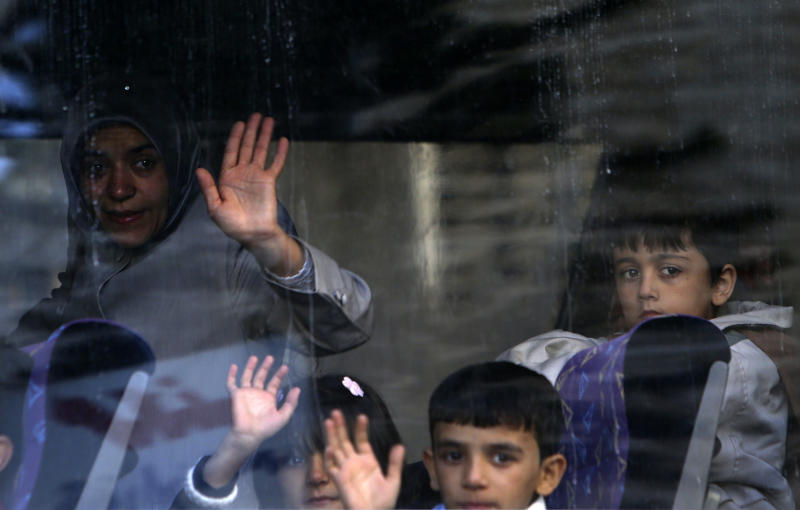 A Syrian refugee family waves to relatives after boarding a bus to Beirut International Airport for a flight to Germany where they have been accepted for temporary resettlement, at the International Organization for Migration office in Beirut, Lebanon, Thursday, Oct. 10, 2013. The dozens of Syrians heading to Germany on Thursday were the second batch of the 4,000 refugees that Germany has accepted to receive on two-year visas while Syria remains mired in a two-year civil war that has killed over 100,000 people, displaced 5 million within their own country, and prompted another 2 million people to flee the country as refugees. (AP Photo/Hussein Malla)