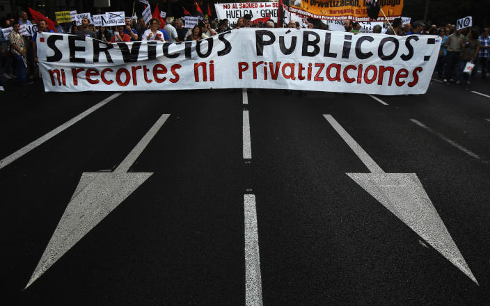 """Protestors hold a banner reading """"public services, no financial cuts, no privatization"""" as they shout slogans against healthcare austerity measures announced by the Spanish government in defense of the public healthcare system in Madrid, Spain, Saturday, Oct. 6, 2012. Hundreds of Spaniards concerned with government cuts to healthcare and civil servants hit with another freeze on their wages for next year held a protest in downtown Madrid. (AP Photo/Andres Kudacki)"""