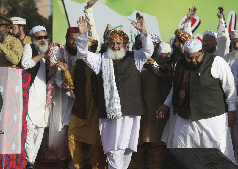Maulana Fazaur Rehman, center, leader of the Muttahida Majlis-e-Amal Alliance waves to his supporters rally against the acquittal of Pakistani Christian woman Asia Bibi, in Karachi, Pakistan, Thursday, Nov. 8, 2018. A Christian woman acquitted after eight years on death row in Pakistan for blasphemy was released but her whereabouts in Islamabad on Thursday remained a closely guarded secret in the wake of demands by radical Islamists that she be publicly executed. (AP Photo/Fareed Khan)