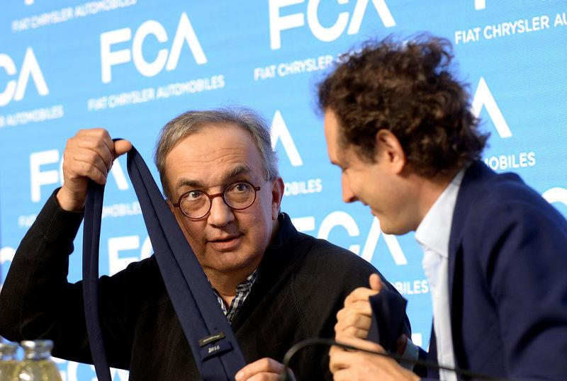 FILE PHOTO: Fiat Chrysler Automobiles CEO Sergio Marchionne jokes with a tie next to chairman John Elkann during media conference in Balocco