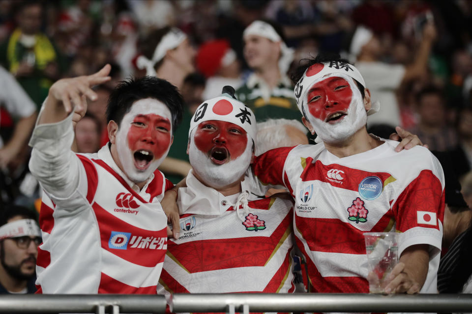 FILE - In this Oct. 20, 2019, file photo, fans cheer during the Rugby World Cup quarterfinal match at Tokyo Stadium between Japan and South Africa in Tokyo, Japan. The start of the Japanese Top League season will be pushed back until next month after 62 players and staff from six teams tested positive for the coronavirus, the Japan Rugby Football Union said Thursday, Jan. 14, 2021.(AP Photo/Jae C. Hong, File)