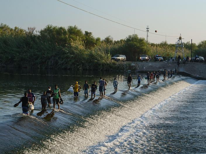 Haitian migrants cross the Rio Grande to get food and supplies near the Del Rio-Acun?a Port of Entry in Ciudad Acuña, Coahuila state, Mexico on September 18, 2021. - The mayor of Del Rio, Texas declared a state of emergency on September 17, 2021 after more than 10,000 undocumented migrants, many of them Haitians, poured into the border city in a fresh test of President Joe Biden's immigration policy. Del Rio Mayor Bruno Lozano said that the migrants were crowded in an area controlled by the US Customs and Border Patrol (CBP) beneath the Del Rio International Bridge, which carries traffic across the Rio Grande river into Mexico.