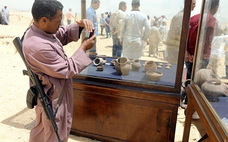 A policeman takes a photograph of objects that were found inside a burial site in Minya, Egypt - Credit: AFP