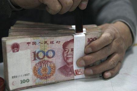 An employee seals a stack of yuan banknotes at a branch of Industrial and Commercial Bank of China in Huaibei, Anhui province April 6, 2011. REUTERS/Stringer/Files