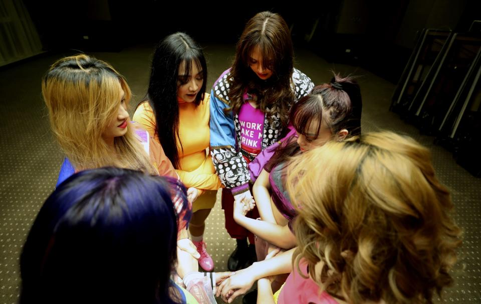 Catherine Gallano, dancer and lead choreographer, 1st left, prays with her group before they start their livestream performance on social media for followers who send them money, in Dubai, United Arab Emirates, Thursday, Nov. 5, 2020. As the coronavirus pandemic mutes Dubai's live-music scene, the Filipino show bands that long have animated the city's storied nightlife are being disproportionately squeezed. Many are out of work and out of money, struggling to survive in overcrowded dormitories at the mercy of employers (AP Photo/Kamran Jebreili)