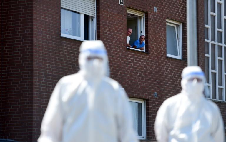 Men look on from a window to personell of a mobile testing unit of the German Red Cross and the German army, prior of testing the employees of the abatoir Toennies, at their residential homes in Verl, Germany, amid the novel coronavirus pandemic. (AFP Photo/Ina FASSBENDER)