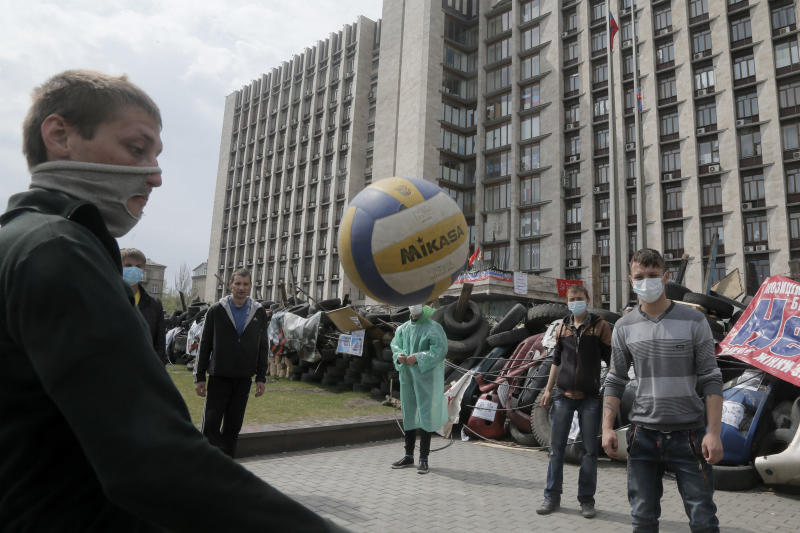 Masked pro-Russian activists play with a ball as they guard a barricade at the regional administration building that they had seized earlier in Donetsk, Ukraine, Saturday, April 19, 2014. Pro-Russian insurgents defiantly refused Friday to surrender their weapons or give up government buildings in eastern Ukraine, despite a diplomatic accord reached in Geneva and overtures from the government in Kiev. (AP Photo/Efrem Lukatsky)