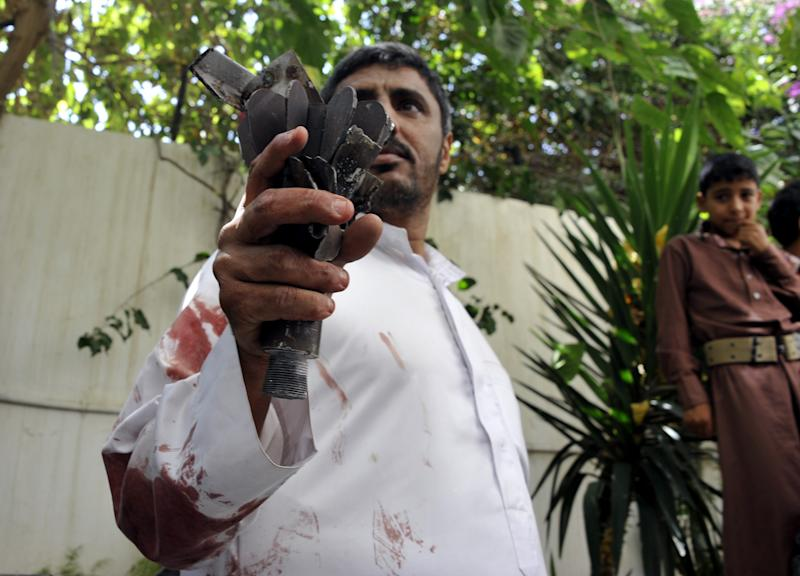 A Yemeni man holds up the remains of a rocket that landed on his home, during clashes between rebels and government forces, in the capital Sanaa on September 19, 2014 (AFP Photo/-)