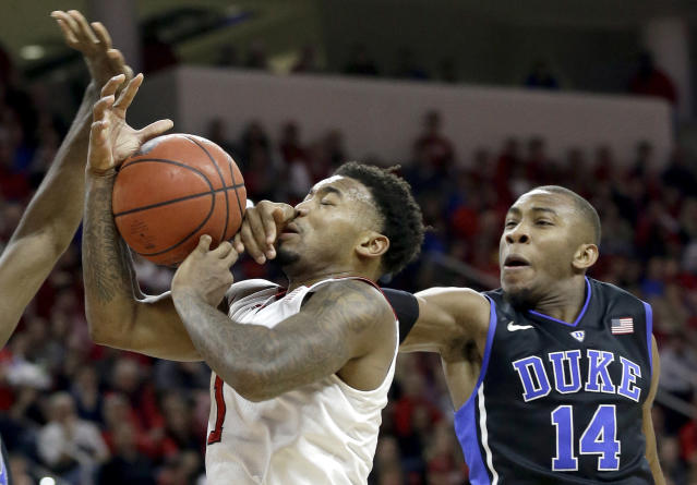 Duke's Rasheed Sulaimon (14) fouls North Carolina State's Trevor Lacey (1) during the first half of an NCAA college basketball game in Raleigh, N.C., Sunday, Jan. 11, 2015. (AP Photo/Gerry Broome)