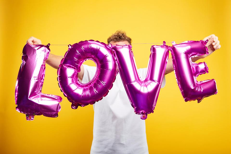 """Man holding balloon letters spelling out """"LOVE"""" (Photo: Getty Images)"""