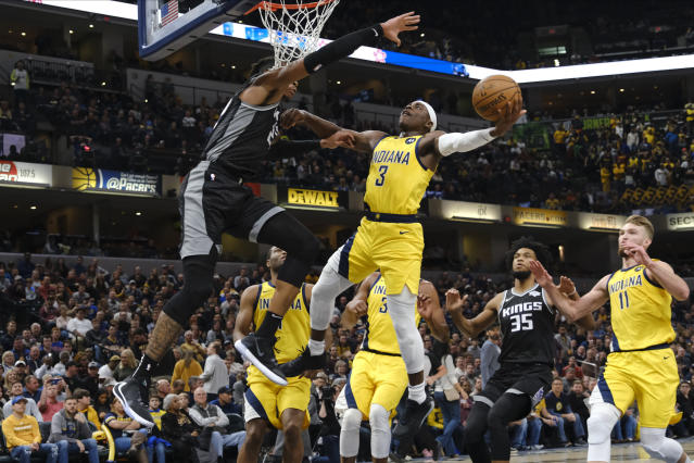 Indiana Pacers guard Aaron Holiday (3) shoots around Sacramento Kings forward Richaun Holmes (22) during the second half of an NBA basketball game in Indianapolis, Friday, Dec. 20, 2019. The Pacers won 119-105. (AP Photo/AJ Mast)