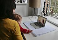 """In this Nov. 26, 2013 photo, Shirin Majid, left, holds her daughter, Ella Townsend, 9 months, as she does a video phone call with her parents, Pirzada and Patricia Majid, from England, in New York. Majid, who works for the internet startup Quirky, is home during her company's quarterly """"blackout"""" week break from work. Quirky's CEO, Ben Kaufman, makes the whole company stop working and take breaks so they don't burn out. (AP Photo/Bebeto Matthews)"""