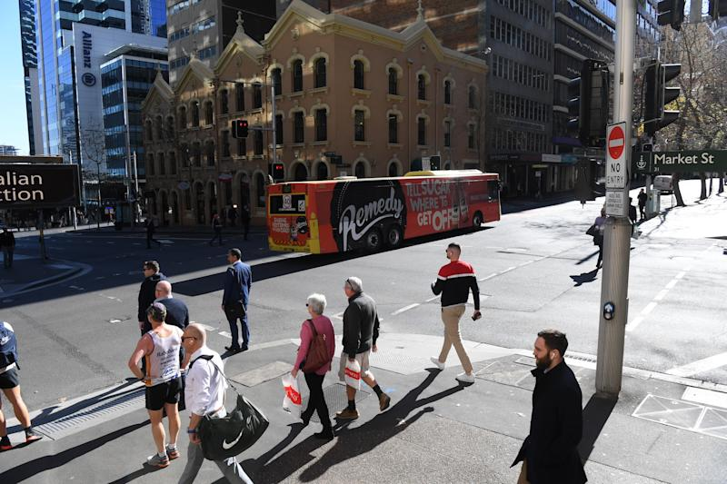 People are seen walking through Sydney's central business district.