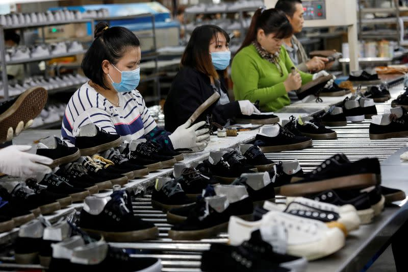 FILE PHOTO: Workers make shoes for export at a factory in Hanoi