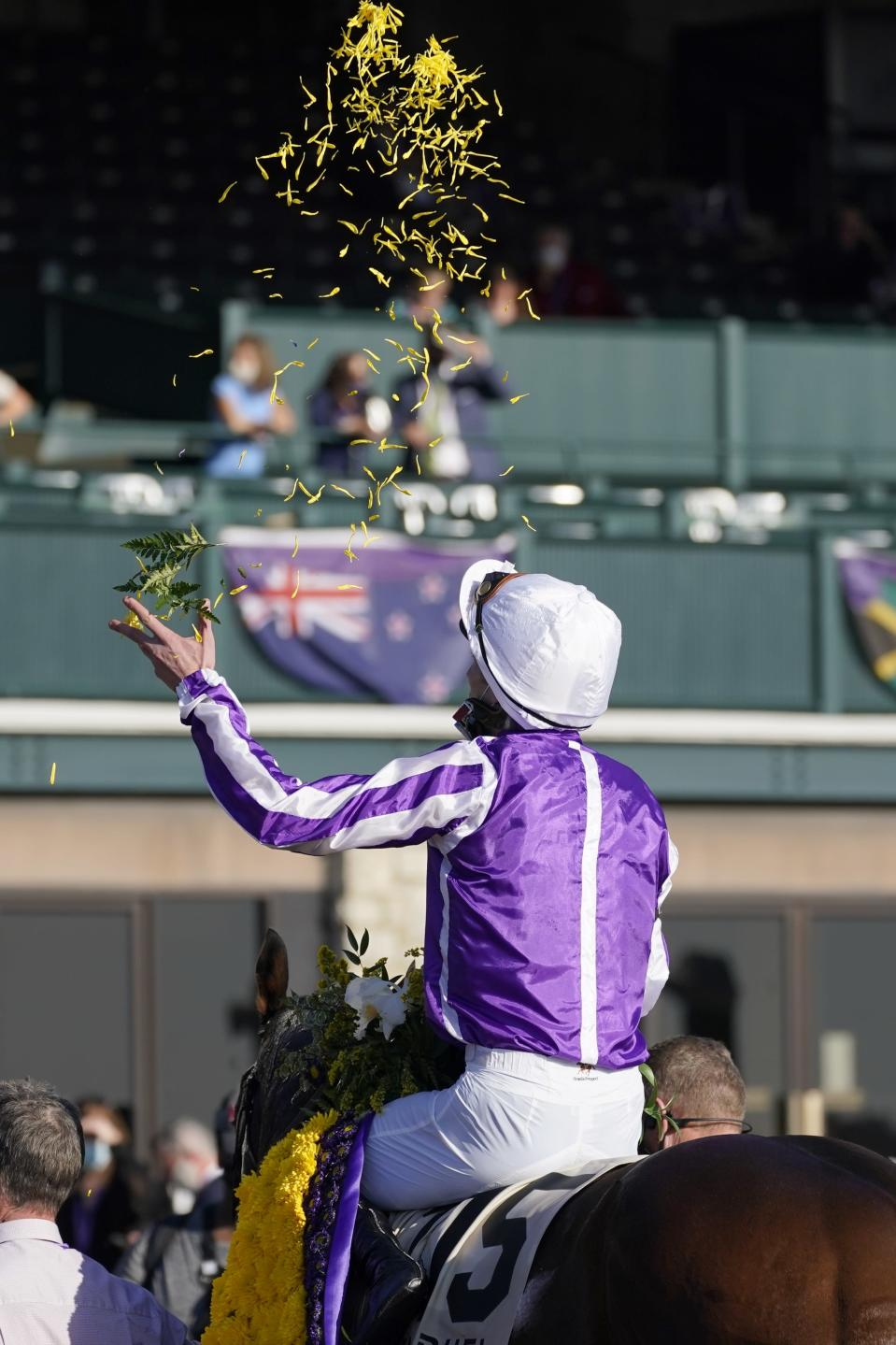 Pierre-Charles Boudot tosses flower pedals in the air in celebration after riding Order of Australia to win the Breeders' Cup Mile horse race at Keeneland Race Course, in Lexington, Ky., Saturday, Nov. 7, 2020. (AP Photo/Darron Cummings)
