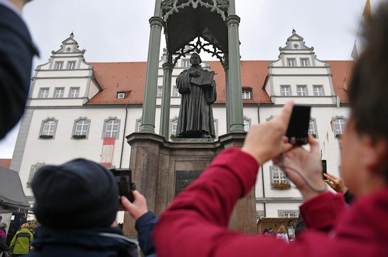 People take pictures of a statue of German Church reformer Martin Luther holding a book including his translation into German of the New Testament of the Bible at the main square in front of the city hall in Wittenberg, eastern Germany, where celebrations take place on the occasion of the 500th anniversary of the Reformation on October 31, 2017.