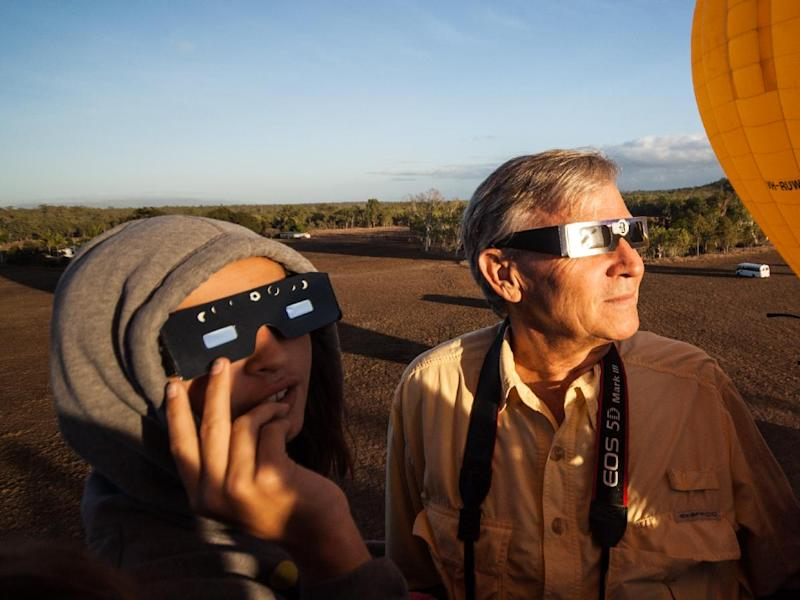 "In this photo released by Hot Air Balloon Cairns, Hank Harper, right, of Los Angeles watches the solar eclipse from a hot air balloon near Cairns, Australia, Wednesday, Nov. 14, 2012. Harper flew to Australia with his two children specially to watch the full eclipse, saying we ""watched the sun's rays re-emerge from behind the moon while kangaroos hopped along the ground below."" (AP Photo/Hot Air Balloon Cairns)"