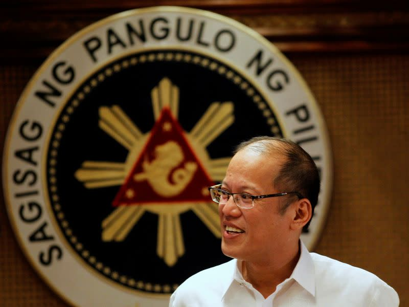 FILE PHOTO - Philippine President Benigno Aquino smiles in front of a presidential seal during a government's oral immunization program for poor families at the presidential palace in Manila