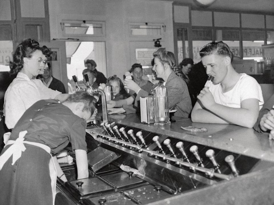 """<p>A teen boy sitting at the parlor counter slurps on an ice cream bar. Popsicles were <a href=""""https://www.history.com/news/ice-cream-boom-1920s-prohibition"""" rel=""""nofollow noopener"""" target=""""_blank"""" data-ylk=""""slk:introduced around the early-1920s"""" class=""""link rapid-noclick-resp"""">introduced around the early-1920s</a> and quickly grew in popularity during the 1920s and '30s.</p>"""