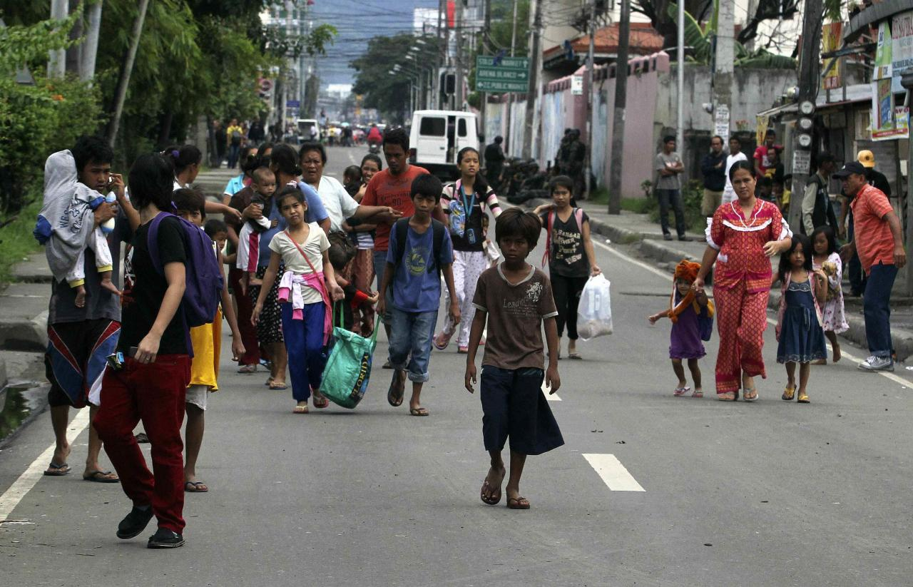 Residents flee from fighting between security forces and rebels from the Moro National Liberation Front (MNLF) who raided several villages in Zamboanga city, southern Philippines September 9, 2013. Rebels took 30 civilian hostages in the southern Philippines on Monday and held security forces in a standoff as part of a drive to derail peace talks, officials said. Police commandos cordoned off parts of Zamboanga City on the island of Mindanao after a rogue faction of the Moro National Liberation Front (MNLF) took hostages and tried to march to the city hall to raise their flag, an army commander said. REUTERS/STRINGER (PHILIPPINES - Tags: POLITICS MILITARY CIVIL UNREST)